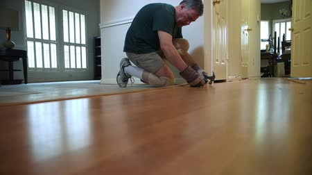 opravář : A homeowner handyman type removing old laminate flooring transition piece in preparation of new floor covering.