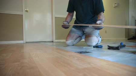 opravář : A homeowner handyman type removing old laminate flooring in preparation of new floor covering.
