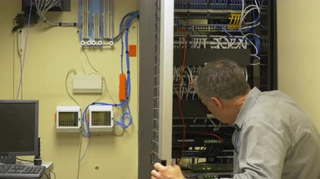 investigar : A network administrator checking patch cables in a server rack as he trouble shoots a problem. Vídeos