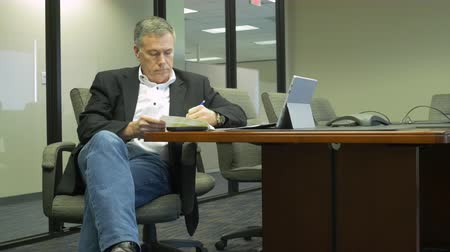 papelada : A mature businessman sitting at a conference table going over some paperwork.