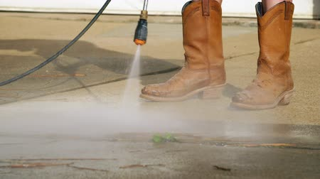 aeróbico : Safety boots are a must for this person using a pressure washer to clean a concrete driveway.