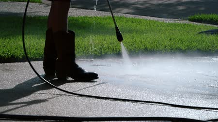 yıkayıcı : Safety boots are a must for this back lit scene of person using a pressure washer to clean a dirty residential concrete driveway. Stok Video