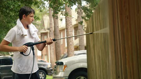 aeróbico : Hard and wet work of this teenage boy power washing a wood fence.