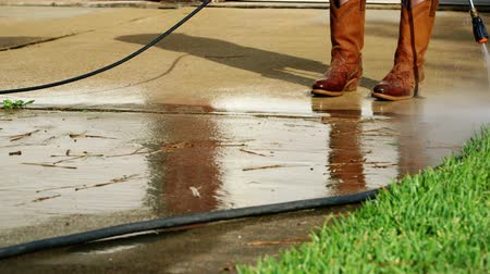 powerful : Safety boots are a must for this person using a pressure washer to clean a dirty residential concrete driveway.