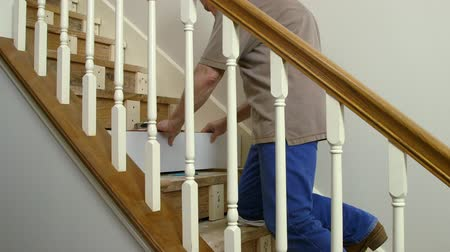 medir : A tradesman or handyman homeowner type fitting in a new riser during a home staircase renovation project. Stock Footage