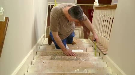 opravář : A tradesman or handyman homeowner type fitting in stair riser and measuring for the tread portion of the step. Dostupné videozáznamy