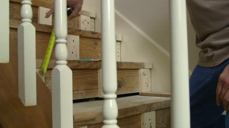 medir : A tradesman or handyman homeowner type taking measurement on a home staircase renovation project.