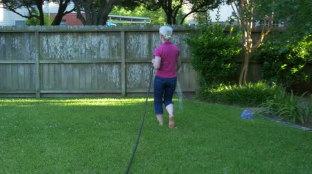 buket : A mature woman watering the plants in her backyard in late afternoon on a pleasant summer day