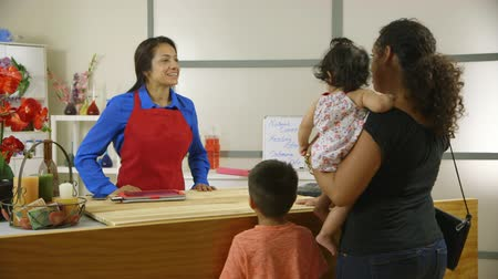 proprietário : Latin American woman small business owner gets pickup order for her regular customer.