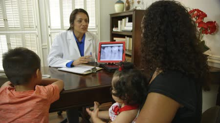hallgat : A Hispanic dentist sitting in her office with a mother and her children going over dental x-ray image displayed on a tablet pc.
