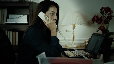 испанец : A Latin American CEO or small business owner working in her office late into the night takes a phone call.