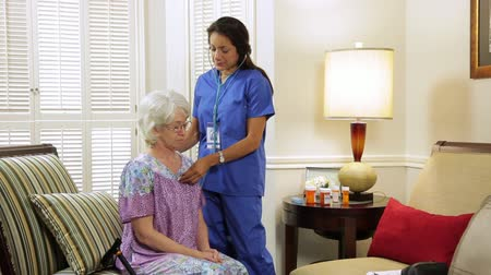 hallgat : A kind and patient Hispanic home health practical nurse checks the lung health of an elderly homebound woman.