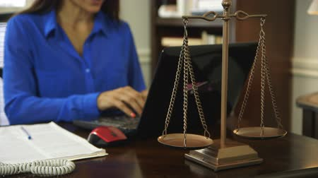 legal : Focus is on scales of justice while woman attorney in office works on laptop in the background.