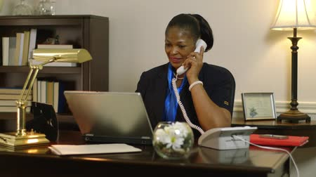 africký : A pretty African American CEO or small business owner sitting in her office take a phone call.