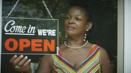 бизнес леди : A lovely smiling African American woman changes the window sign on her small business to open.