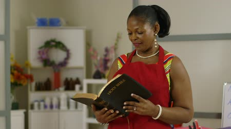 uplifted : Scene pans from shop decor to a lovely Christian African American small business owner reading her Bible.