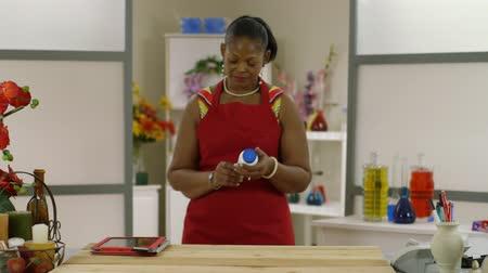 inventário : A lovely African American woman uses a tablet pc to order more inventory for her small business.
