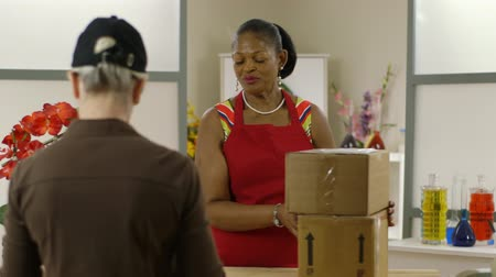 бизнес леди : A lovely African American small shop owner receives and signs for packages that are being delivered.