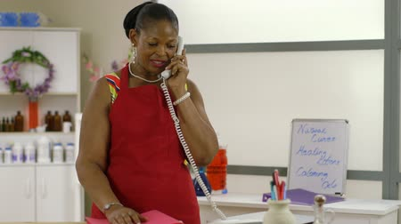 ügy : A lovely African American woman small business owner multi-tasking as she checks her records takes a phone call and helps a customer that enters her shop.