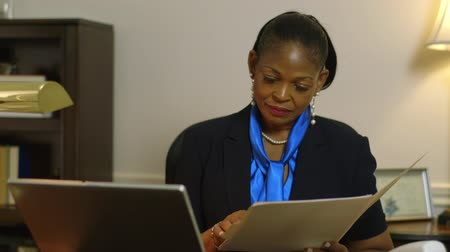 africký : Scene tilts up and focuses a lovely African American corporate CEO or small business owner in office looking over paperwork file.