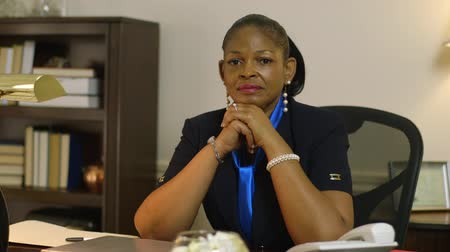 africký : Pensive African American woman corporate CEO or small business owner turns and looks unsmiling at camera.