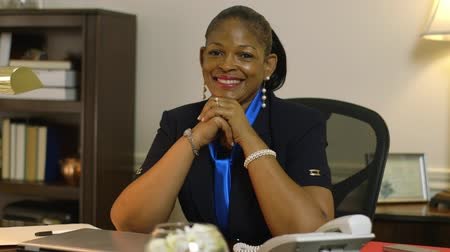 africký : A pensive African American corporate CEO or small business owner in her office turns toward audience and smiles. Dostupné videozáznamy