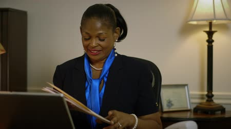 ügy : A pretty African American CEO or small business owner sitting in her office receives a file folder from an assistant.