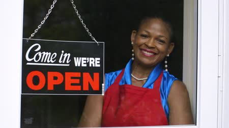 A lovely African American woman changes the window sign on her small business from closed to open then smiles a great smile.