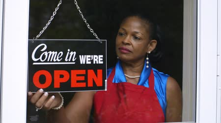 бизнес леди : A lovely African American woman changes the window sign on her small business from closed to open.