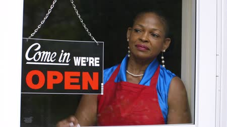 владелец : A lovely African American woman changes the window sign on her small business from closed to open then checks the time.