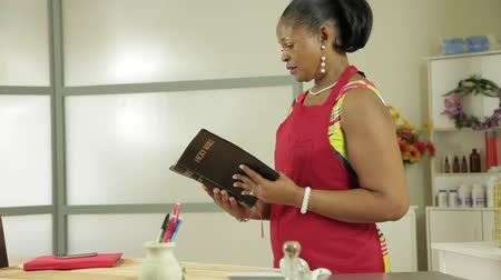 uplifted : Lovely African American small business shop owner takes time to read from her Bible. Stock Footage