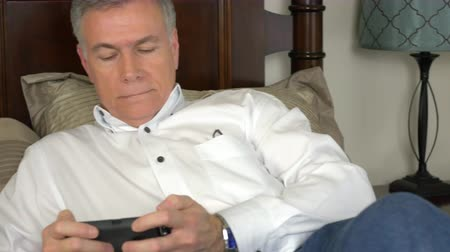 vigyorgó : A contented mature man relaxing on his bed using his smart phone to send a text message or email. Stock mozgókép