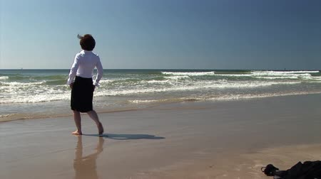 empresária : businesswoman drops her coat and laptop and plays in the surf