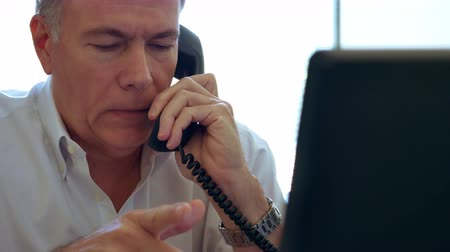 adam : A mature man in his office takes a phone call on a desk phone