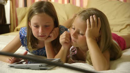 кровать : Two little girl friends laying on a bed quietly playing a game on a tablet pc. Стоковые видеозаписи