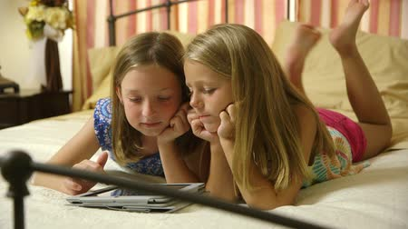 кровать : Two little girls laying on a bed quietly playing a game on a tablet pc.