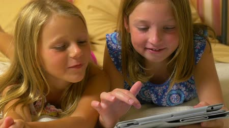 кровать : Two little girls lying on a bed are happily entertained by playing a game on a tablet pc. Scene tracks left. Стоковые видеозаписи