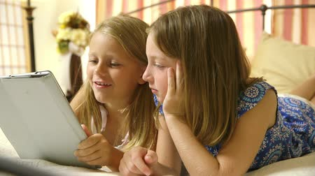 o : Two young sisters in their bedroom quietly playing a game on a tablet pc.