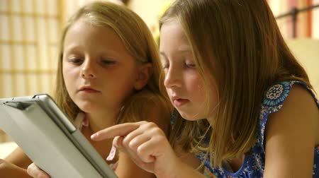 harmonie : Two friends or sisters share and take turns as they see who can win the game they are playing on a tablet pc.