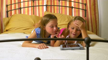 o : Two little girls lying on a bed are entertained by playing a game on an electronic tablet pc.