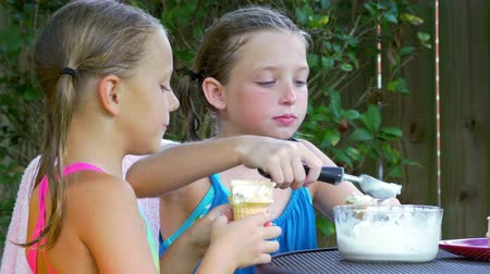 pigtailler : Two cute little girls with wet ponytails enjoy eating a cool creamy ice cream treat outside under a shade tree. 4K footage Stok Video
