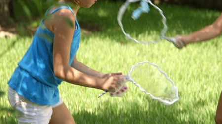 pigtailler : Two cute little girls in their backyard trying to make giant bubbles with homemade wands and soapy solution.