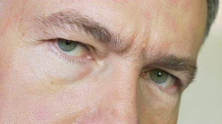 arcszín : A close-up of the eyes of a mature Caucasian male looking quite seriously at the viewer. Stock mozgókép