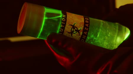 espécime : A large vile of green luminescent liquid is labeled as a biohazard held by someone wearing hazmat type gloves. Vídeos