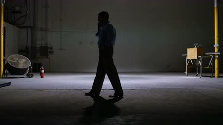 tek başına : A man on a cell phone pacing in the lone light of a large dark empty warehouse.
