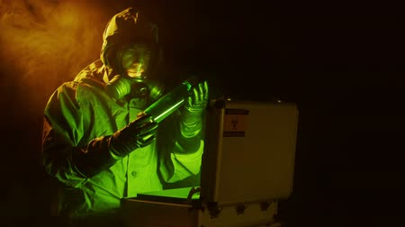 espécime : A man dressed in a military grade hazmat suite examines a green luminescent liquid he lifts out of a case.