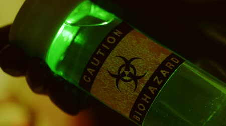 espécime : A large vile of green luminescent liquid is labeled as a biohazard being held by someone wearing hazmat type protective gloves. Vídeos