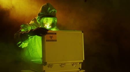 espécime : A man dressed in military grade hazmat suit places a biohazard sample into a protective case then surveys the scene.