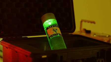 ürpertici : A black case with a large vile of green luminescent liquid labeled as a biohazard. Stok Video