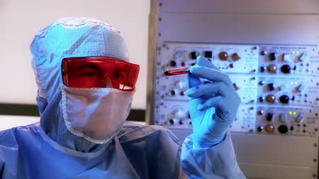 espécime : A technician working in a clean room visually examines a sample of blood in a vile.